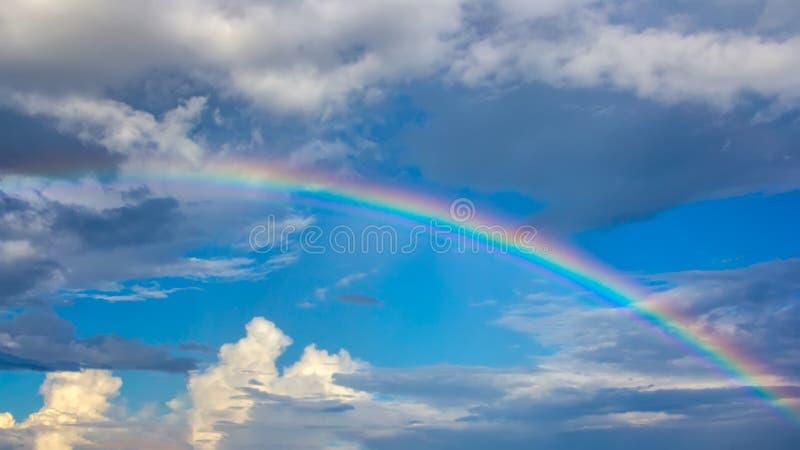 Regenboog over blauwe hemel met wolken stock afbeelding