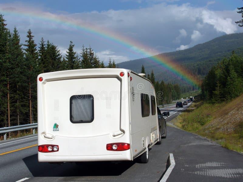 Regenboog over de caravan stock afbeelding
