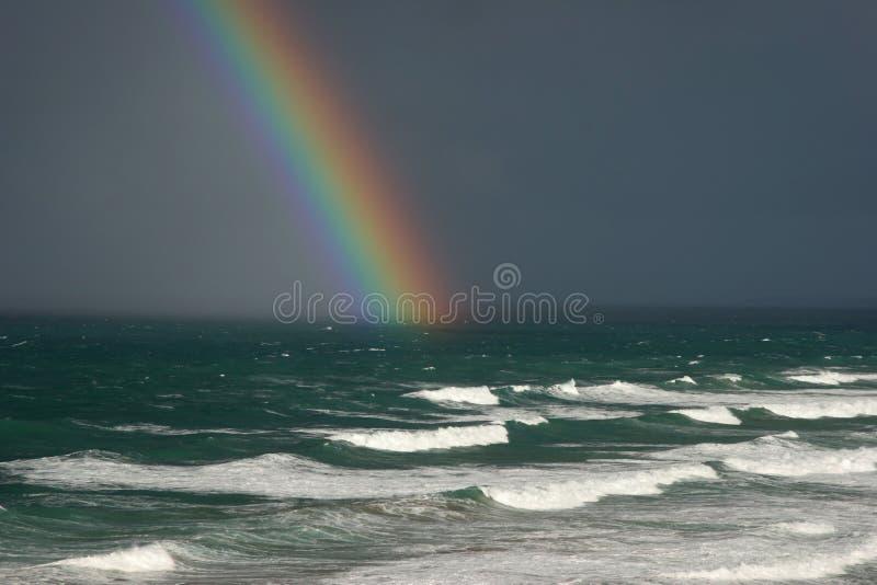 Regenboog over de oceaan stock foto's