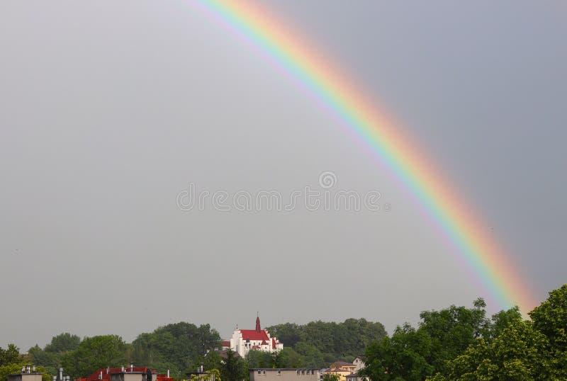 Regenboog over de tempel in een donkere en regenachtige hemel Ongunstige weersomstandigheden Een mooi atmosferisch fenomeen van b stock fotografie
