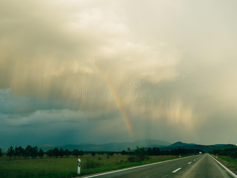 Regenboog over de weg stock foto