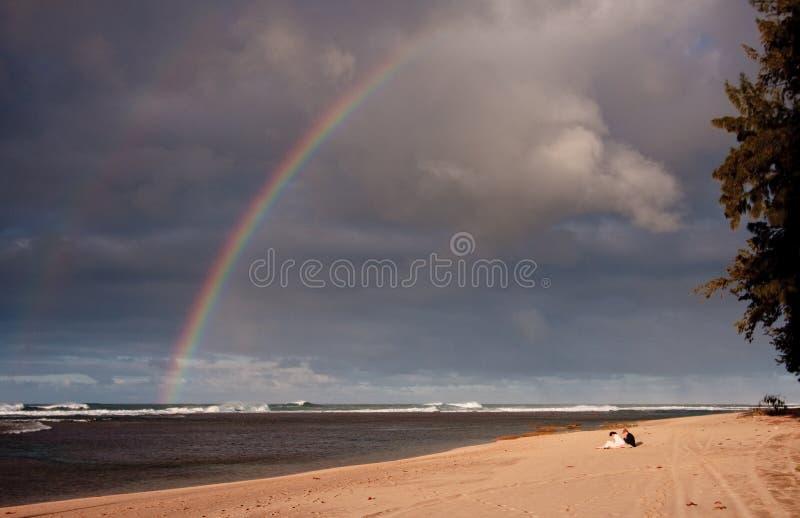 Regenboog over een breed zandig strand royalty-vrije stock foto's