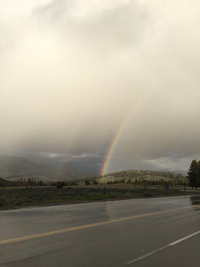 Regenboog over een natte weg met bewolkte hemel royalty-vrije stock afbeeldingen