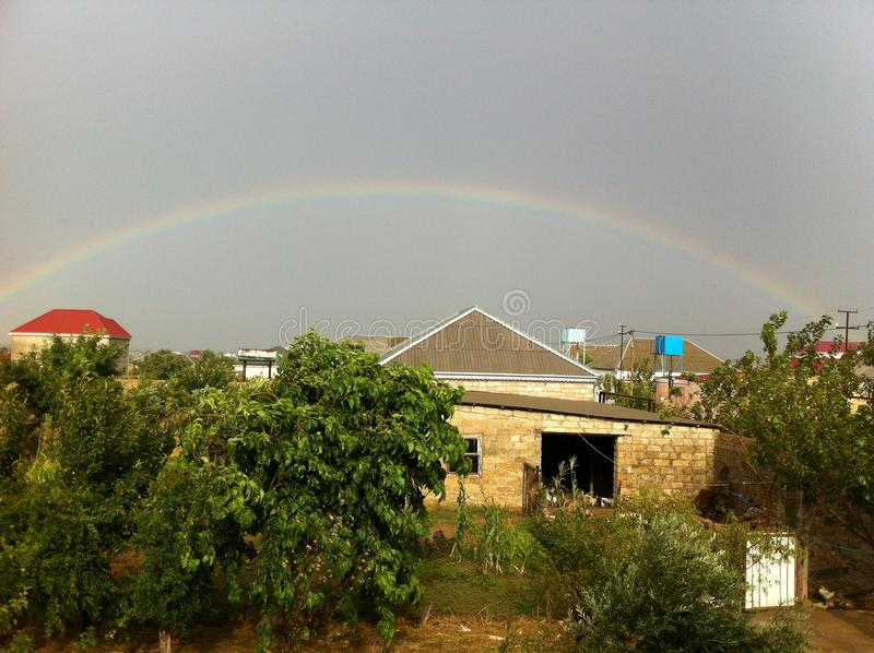 Regenboog over het dorp royalty-vrije stock foto