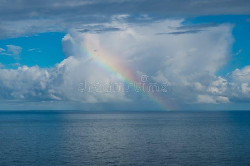 Regenboog over oceaan stock foto