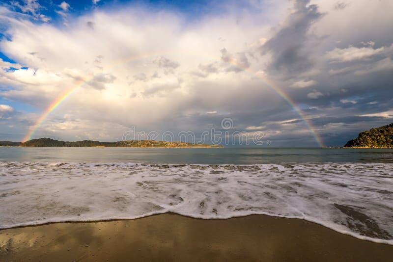 Regenboog over oceaan en strand tegen bewolkte hemel royalty-vrije stock fotografie