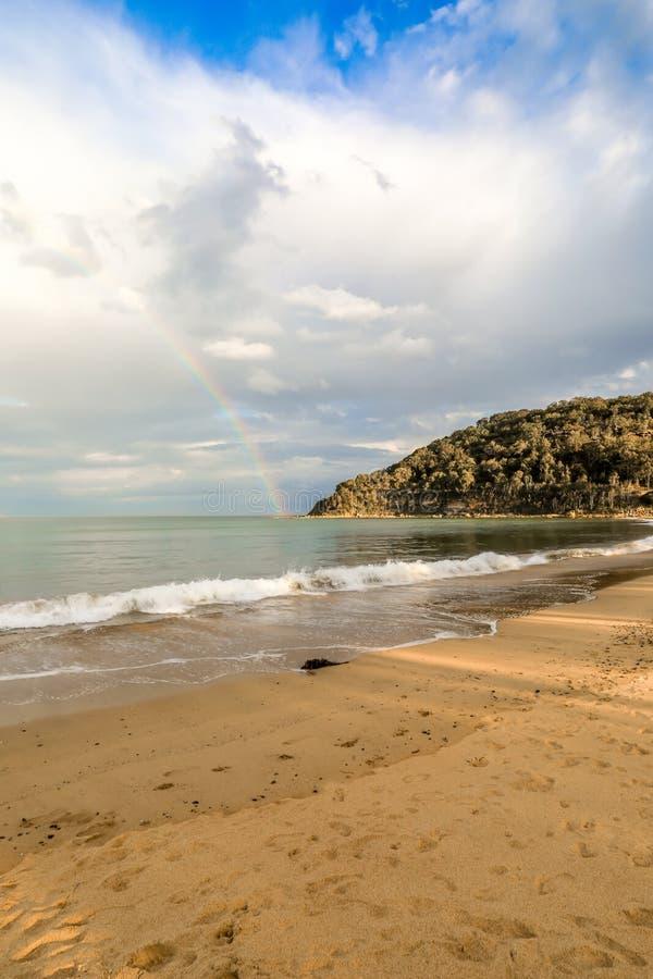Regenboog over oceaan en strand tegen bewolkte hemel royalty-vrije stock afbeeldingen