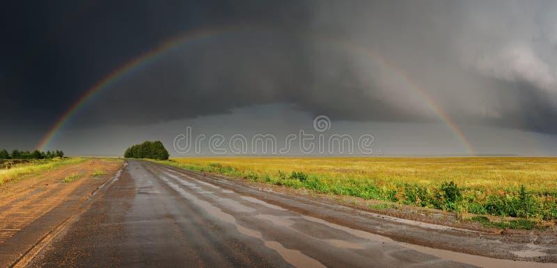 Regenboog over weg stock afbeelding