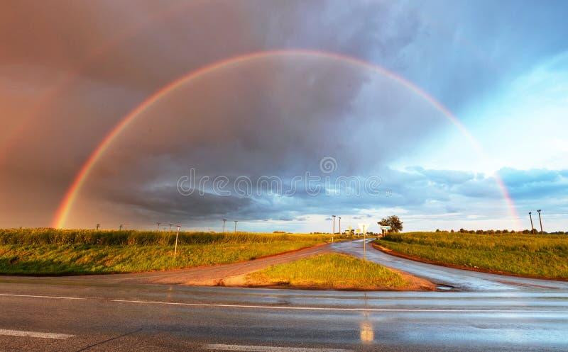 Regenboog over weg royalty-vrije stock afbeeldingen