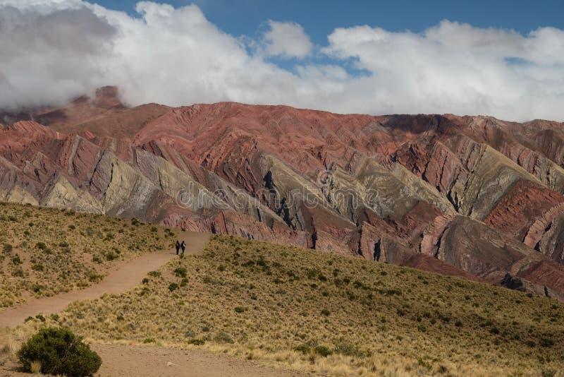 Regenboogbergen en vallei in Humahuaca Argentini? met wandelaars stock foto