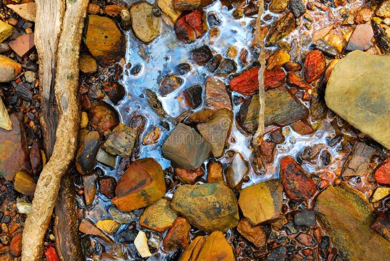 Regenboogbezinning van ruwe oliemorserij op de steen stock afbeelding