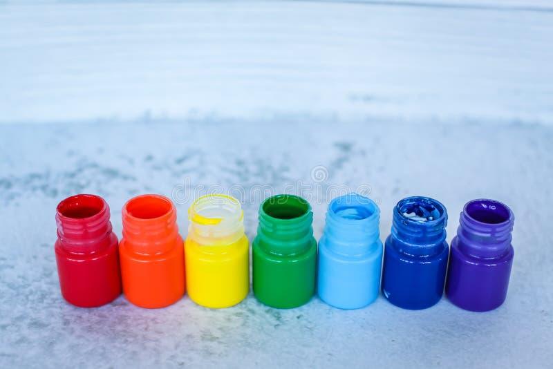Regenbooggouache of acrylverven in kruiken op witte grungeachtergrond, selectieve nadruk stock fotografie
