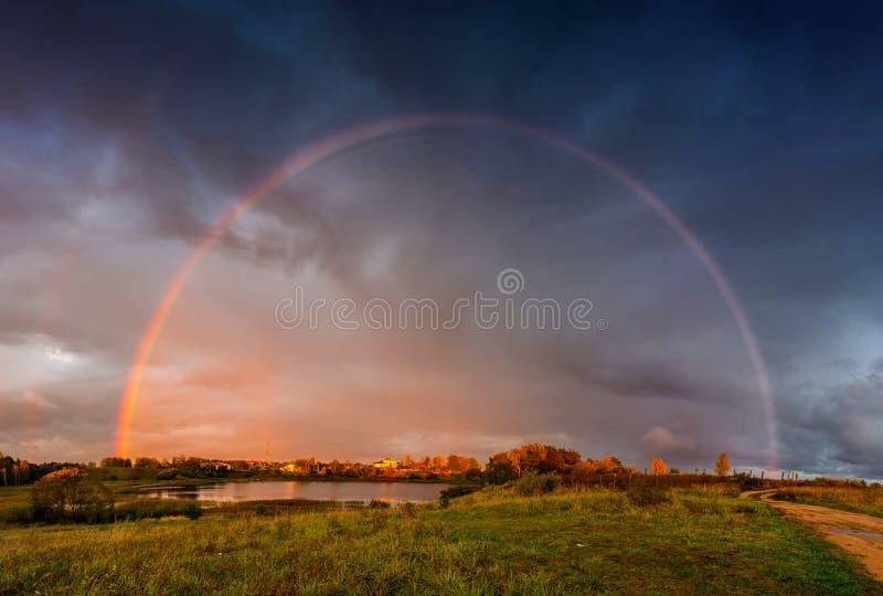 Regenbooglandschap en dramatische regenhemel stock afbeelding
