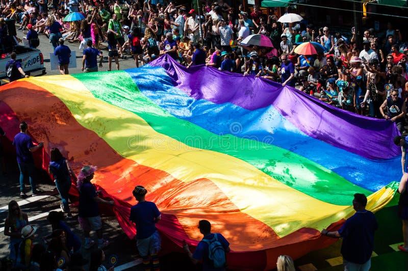 Regenboogvlag door mensen wordt gedragen die schenkingen verzamelen tijdens trotsparade die royalty-vrije stock afbeelding