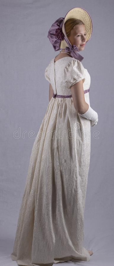 Regency woman in cream dress and bonnet on studio backdrop stock image