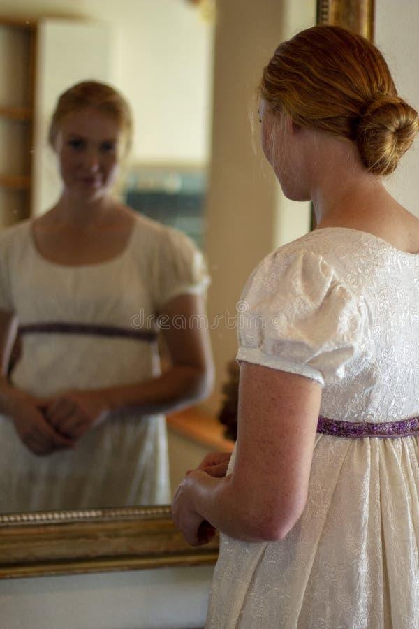 Regency woman in cream dress looks in a gold framed mirror royalty free stock image