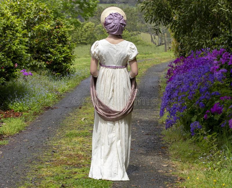 Regency woman in a cream dress, paisley shawl and bonnet stock photography