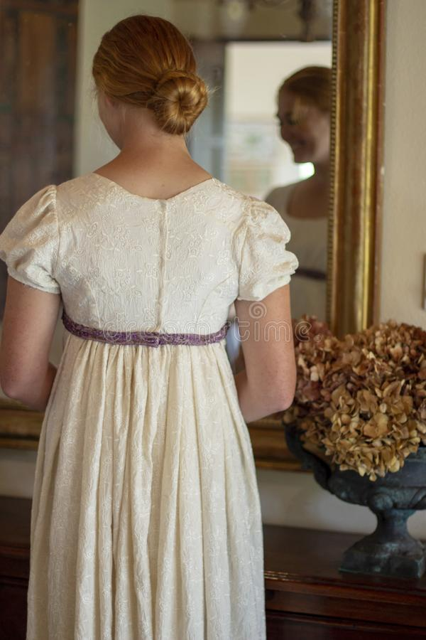 Regency woman in cream dress stands before a mirror stock photo