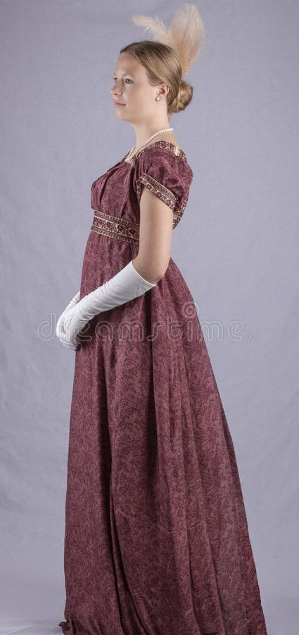 Regency woman in a red dress on studio backdrop royalty free stock photos