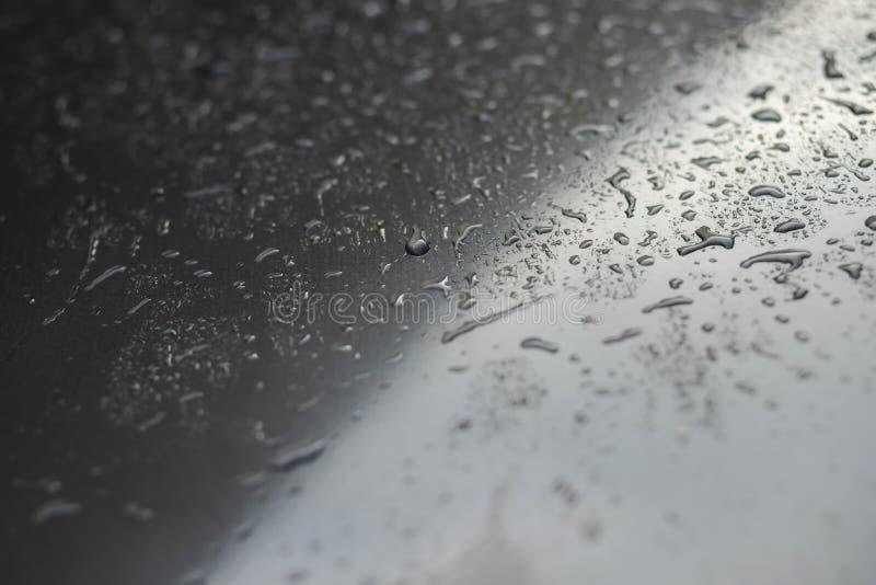 Regendalingen en dauw waterdalingen op een grijs autodak na het tegengehouden regenen, selectieve nadruk waterdichte oppervlakte stock fotografie