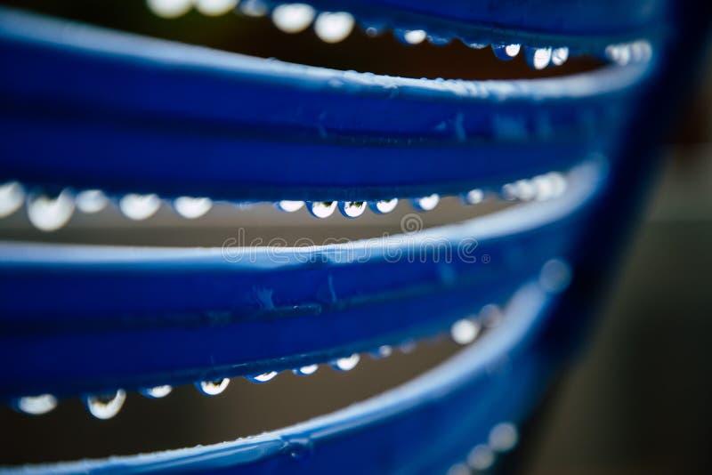 Regendalingen op blauwe omheining royalty-vrije stock afbeeldingen