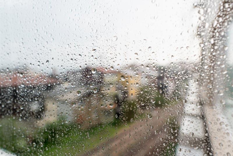 Regendalingen op de oppervlakte van vensterglazen met stadsachtergrond Natuurlijk die Patroon van regendruppels op stedelijke ach royalty-vrije stock foto's