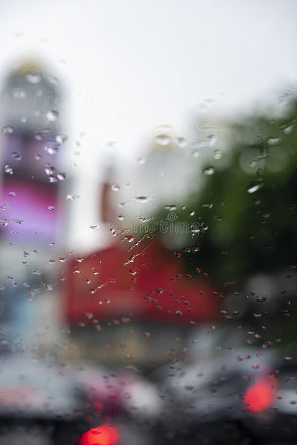 Regendalingen op een voordieautowindscherm, van een voorzetel van een auto in een ochtend wordt gezien stock fotografie