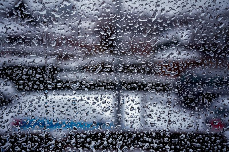 Regendalingen op glazen vensteroppervlakte met bewolkte achtergrond stock foto