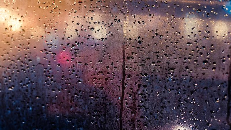 Regendalingen op venster Abstract verkeer in regenende dag Mening van autozetel stock afbeeldingen