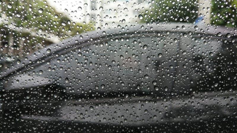 Regendalingen op venster met auto royalty-vrije stock afbeelding