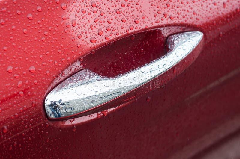 regendalingen op verchroomd handvat van rode luxeauto royalty-vrije stock fotografie