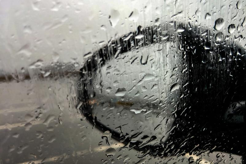 Regendruppel buiten de auto in regenende dag bij autoparkeren Goede mening van bestuurderszetel stock afbeelding
