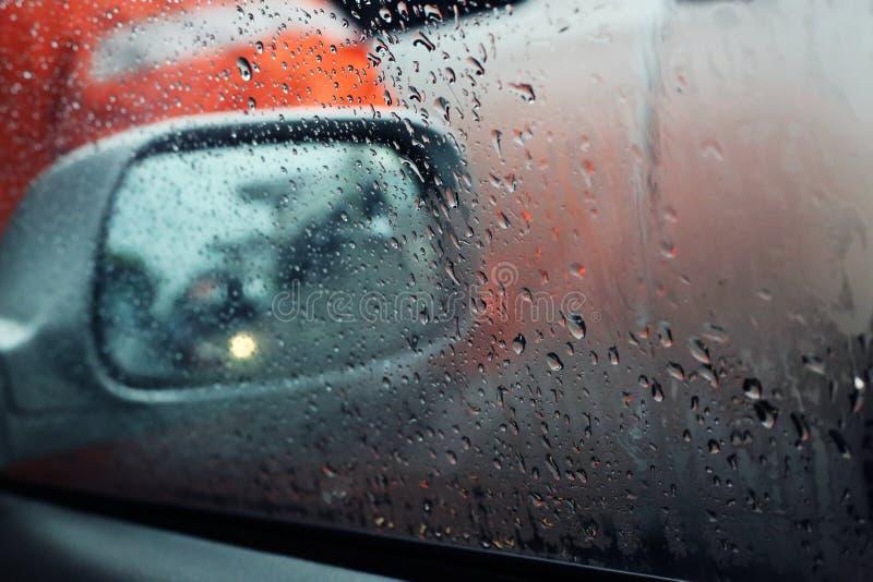 Regendruppels bij het autoraam stock afbeelding