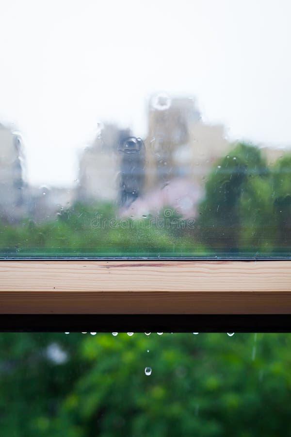 Regendruppels en water het gieten op een venster stock afbeelding