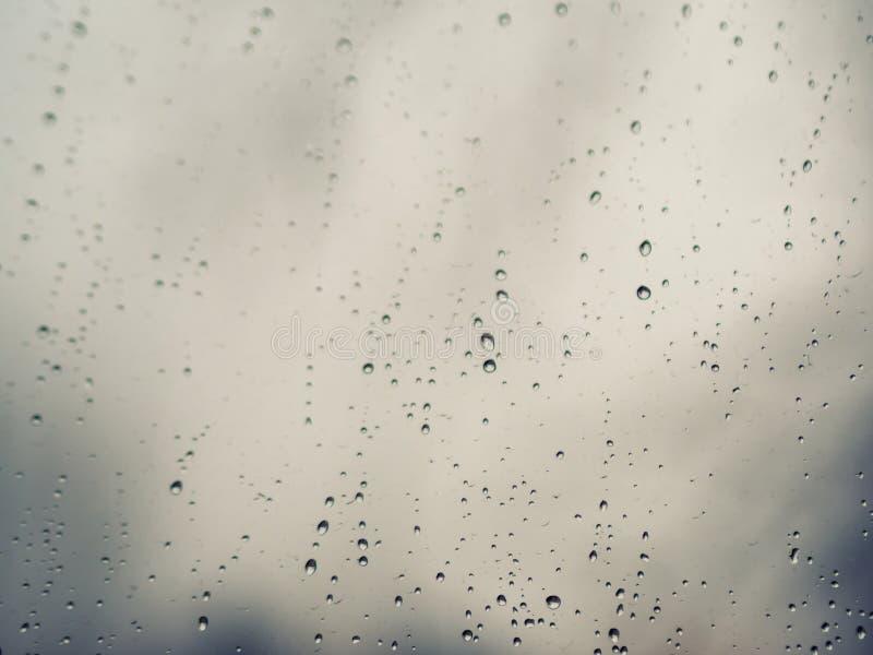 Regendruppels op de oppervlakte van glazen venster stock afbeelding