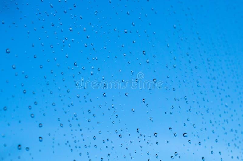 Regendruppels op de oppervlakte van glazen venster stock foto