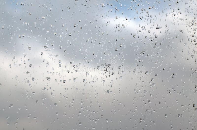 Regendruppels op een ruit op een regenachtige dag, textuurachtergrond stock foto
