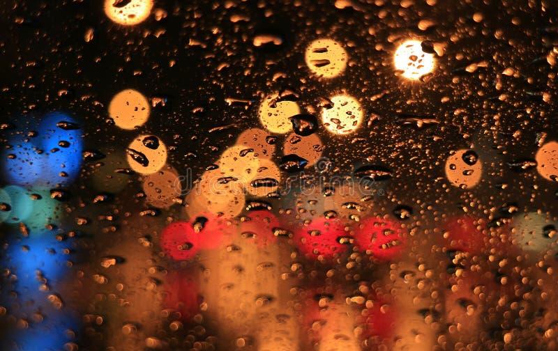 Regendruppels op het autowindscherm met vage uithangbordlichten langs de stedelijke straat bij nacht royalty-vrije stock fotografie