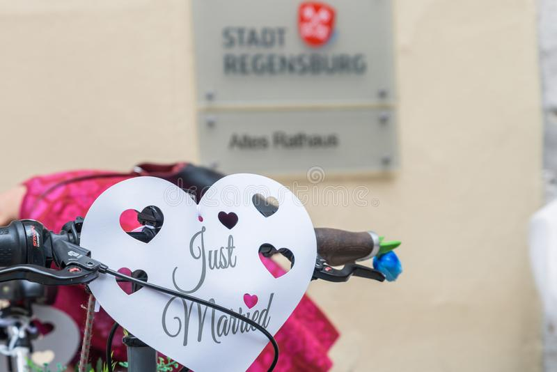 Close-up of a bicycle decorated with wedding jewellery in front of the old registry office in Regensburg with the sign and German royalty free stock photos