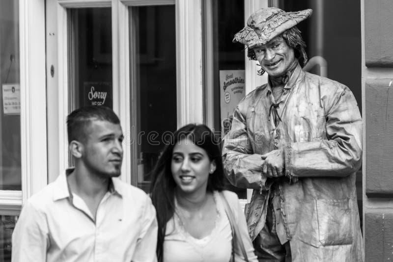 Regensburg Bayern, Tyskland, Augusti 22, 2017: Gatakonstnär som en bosatt staty i den fot- zonen i Regensburg, Tyskland royaltyfri fotografi