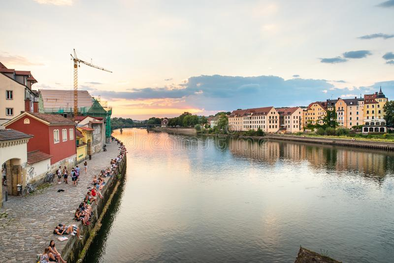 Regensburg Tyskland - 26 Juli, 2018: Folket har att vila på den Danube River banken härlig solnedgång Populära turist- destinatio arkivbilder
