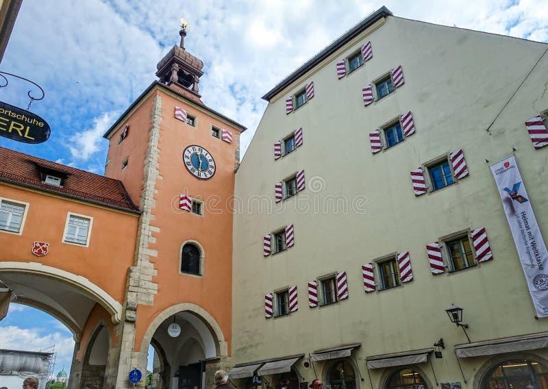 Regensburg Tyskland - Juli, 09 2016: Klockatorn och medeltida byggnad i stadsingången från stenbron arkivbilder