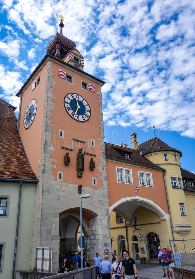 Regensburg Tyskland - Juli, 09 2016: Sikt av klockatornet framme av bron arkivfoton