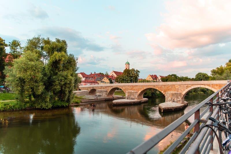 Regensburg Tyskland - 26 Juli, 2018: Spång stenbron över Danubet River Gammal kloster och kyrklig komplex St-man arkivbild