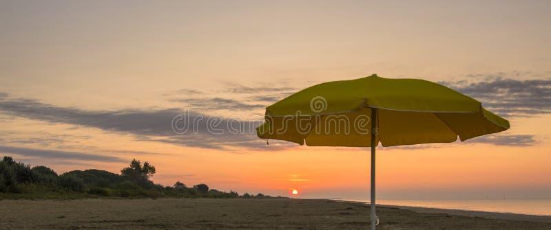 Regenschirm auf dem Strand bei Sonnenuntergang lizenzfreie stockbilder