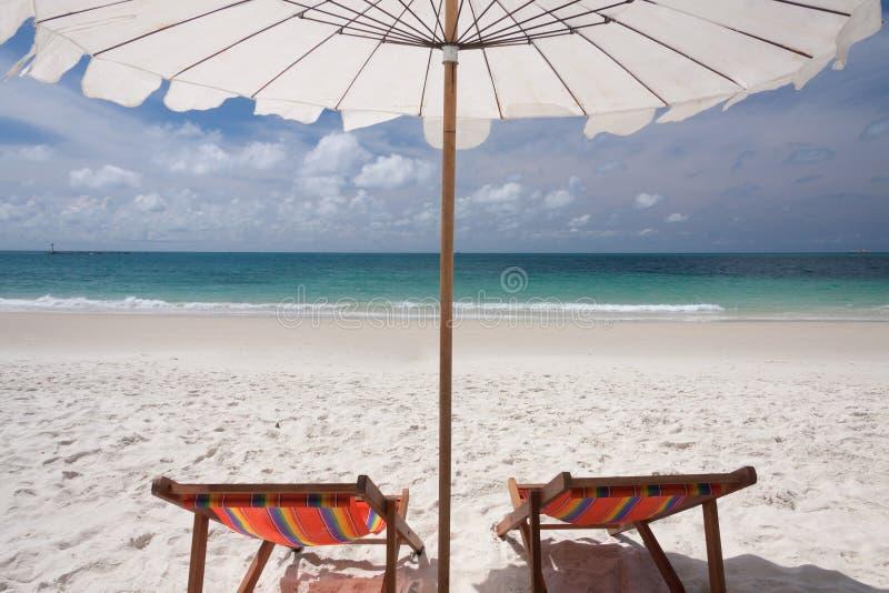 Regenschirm und Doppelstühle stockbild