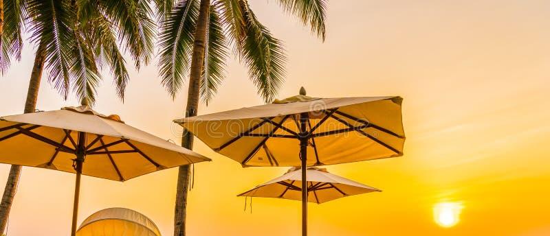 Regenschirm und Stuhl auf dem sch?nen Strand und Meer zur Sonnenaufgangzeit f?r Reise und Ferien stockfoto