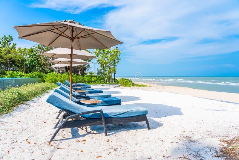 Regenschirm und Stuhl auf dem Strandseeozean mit blauem Himmel und wei?er Wolke stockfoto