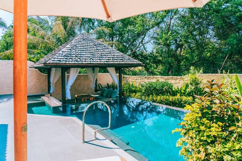 Regenschirm und Stuhl um Ozeanstrand des Swimmingpools neary Seemit blauem Himmel und wei?er Wolke lizenzfreies stockfoto