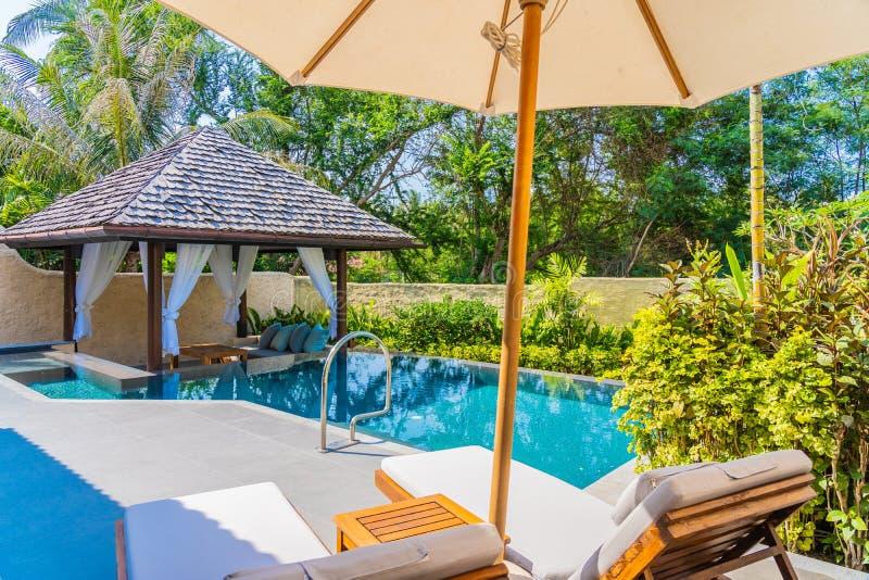 Regenschirm und Stuhl um Ozeanstrand des Swimmingpools neary Seemit blauem Himmel und wei?er Wolke stockfotos